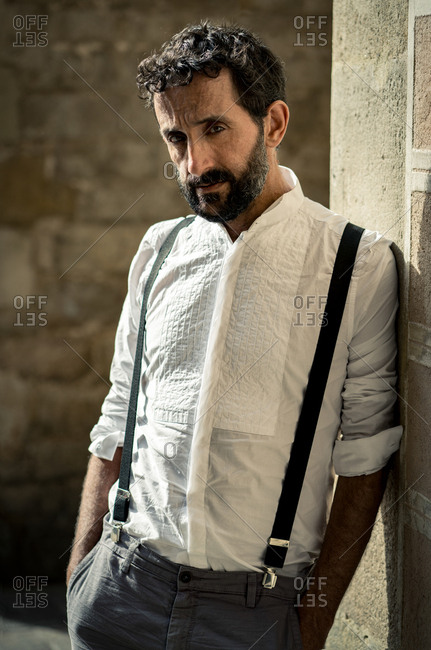 Middle-aged bearded serious man in shirt and suspenders holding hands in pockets and leaning on wall looking at camera outdoors