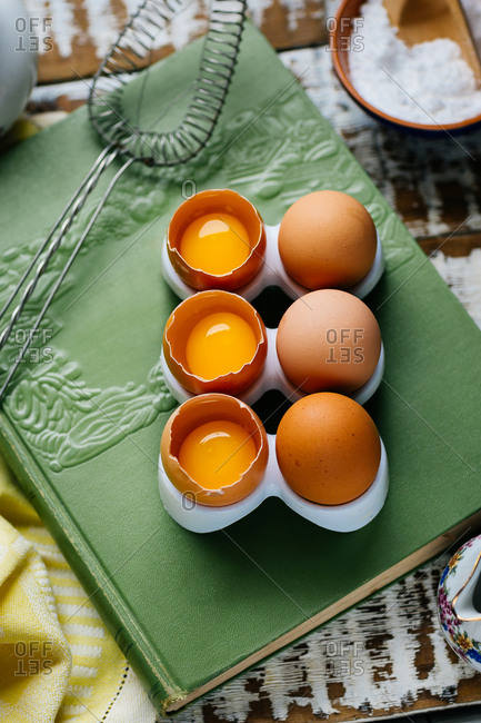 From above stand with whole and cracked eggs on green book.