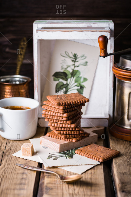 Stack of sweet tasty cookies and cup of coffee on a table.