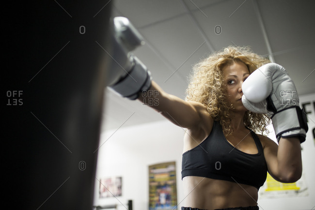 Serious woman training in gym with punching bag