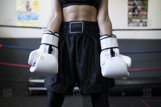Faceless woman in sport wear staying in gym with professional equipment