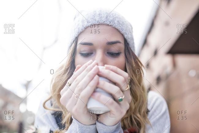 Woman enjoying drink in outside cafe