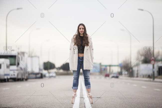 woman dancer in ballet tips, jeans and white coat on the street