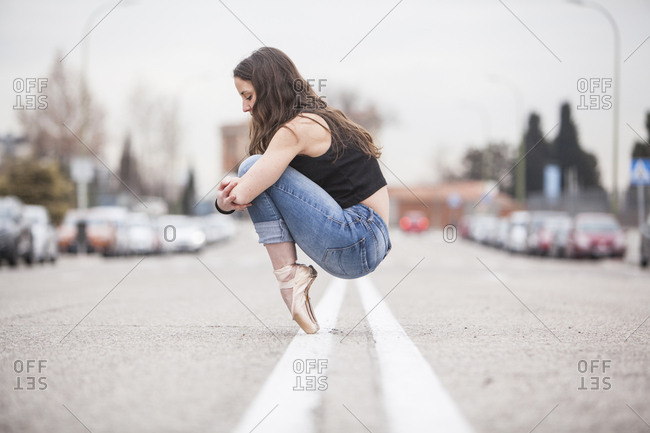 Ballerina on her point shoes hugging her knees in the middle of the street