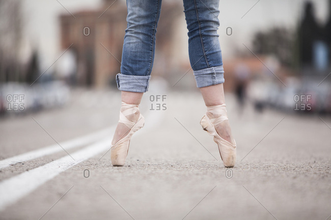 woman dancer on ballet tips and jeans on the street and legs apart