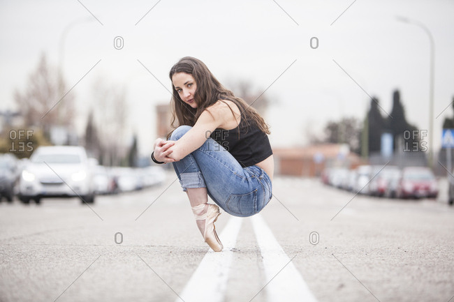 woman dancer on ballet tips and jeans on the street and hugging his knees