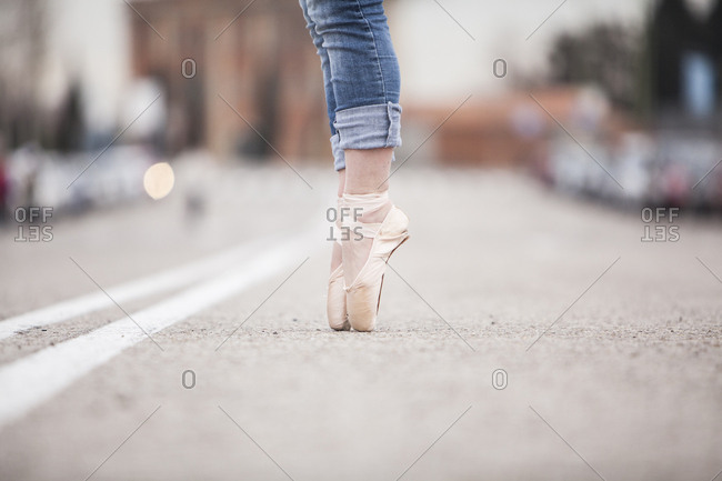 woman dancer on ballet tips and jeans on the street