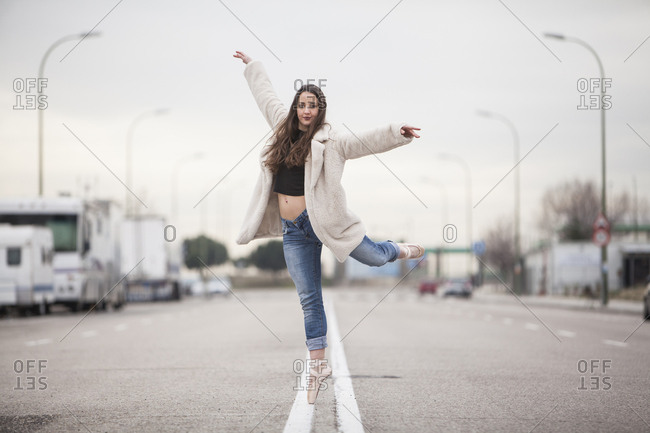woman dancer on one ballet tips, jeans and white coat on the street