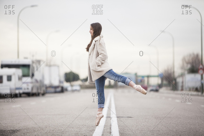 woman dancer on one ballet tips, jeans and white coat on the street and look down vertical format