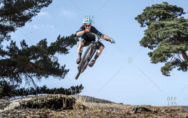 Mountain biker performing jump on bicycle on single track in forest