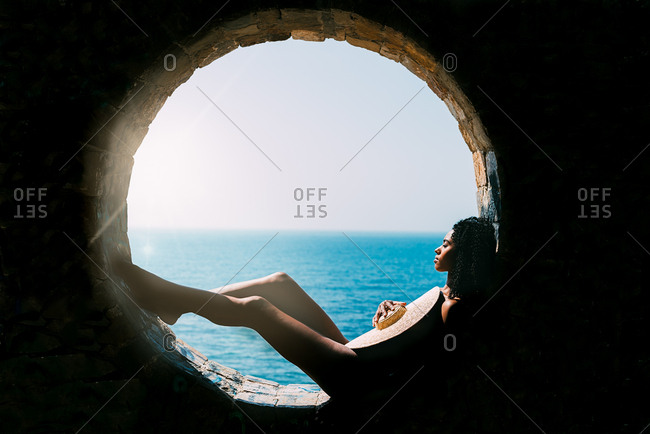 Naked woman leaning back contemplating the sea view