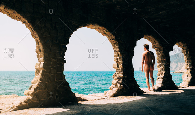 Naked man contemplating the sea view