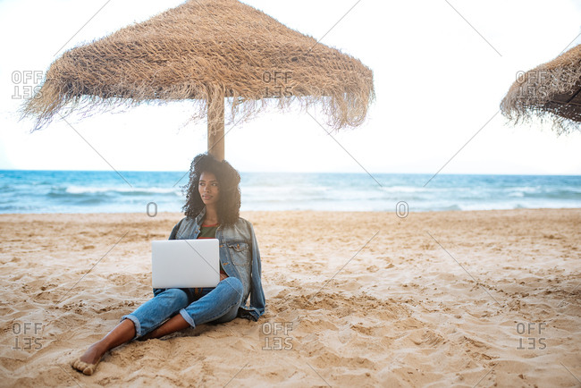 woman leaning on a straw umbrella at the beach working on the computer