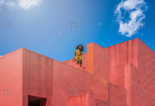 Black woman standing in a colorful geometric building roof terrace