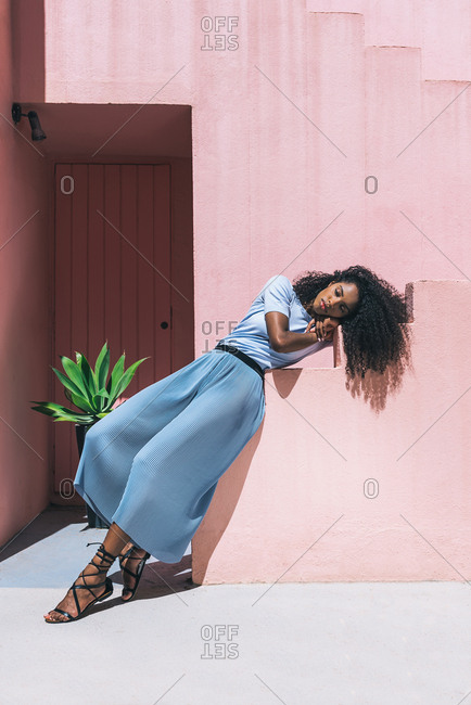 Black woman lying in a colorful geometric building stairs