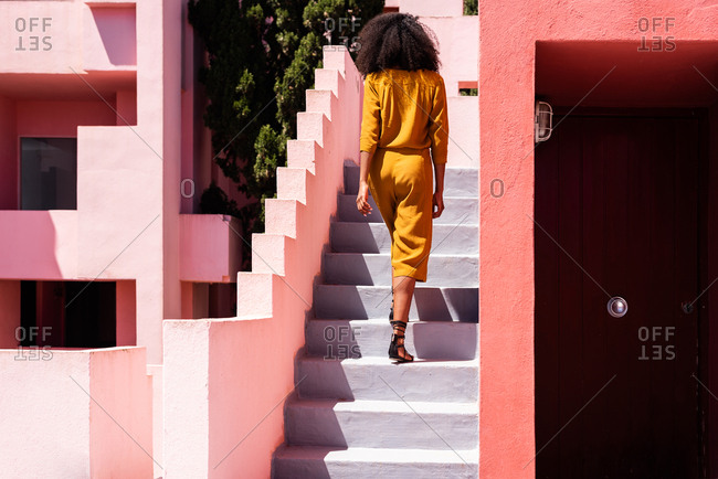 Black woman walking up in a colorful geometric building stairs