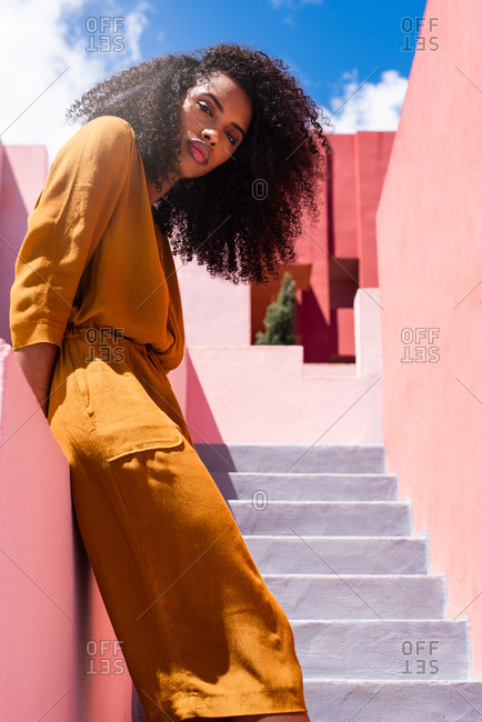 Black woman leaning in a colorful geometric building wall