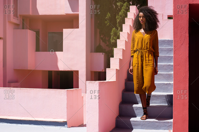 Black woman walking down in a colorful geometric building stairs