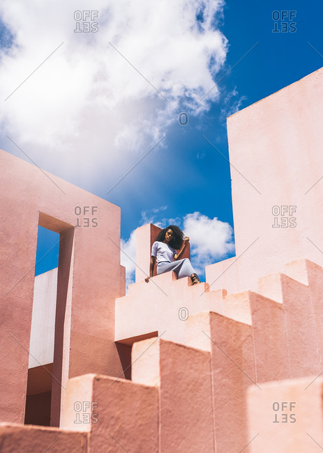 Black woman sitting in a colorful geometric building terrace