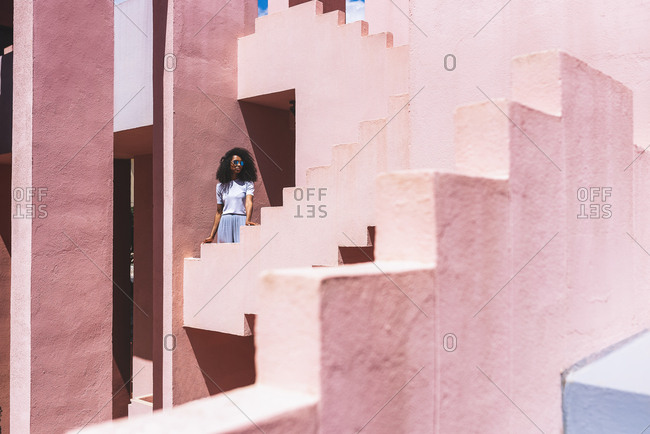 Black woman in a colorful geometric building stairs