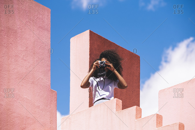 Black woman in a colorful geometric building taking a picture with a vintage camera