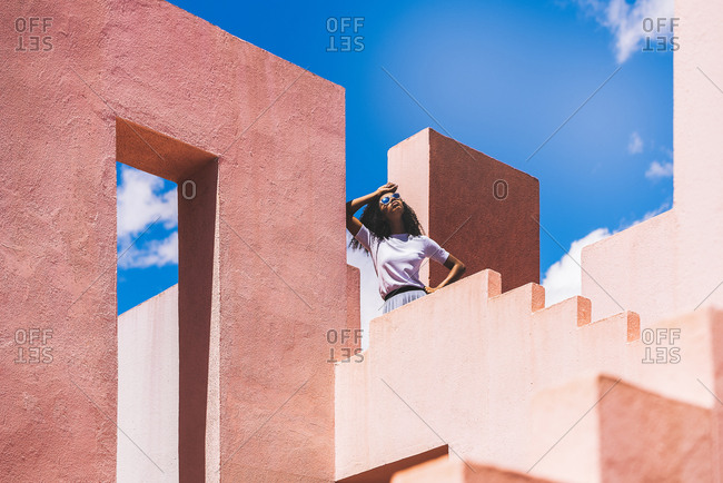 Black woman in a colorful geometric building with sunglasses