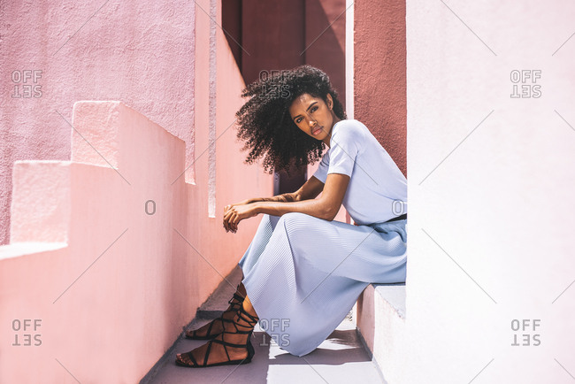 Black woman sitting in a colorful geometric building