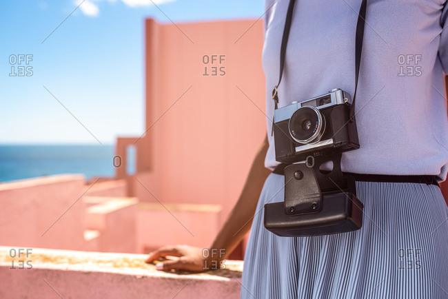Black woman in a colorful building with a vintage camera
