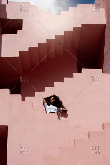 Black woman relaxing in a colorful geometric building stairs