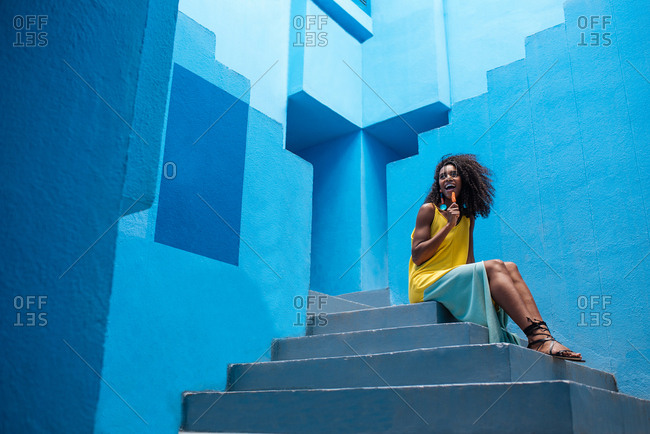 Black woman sitting in a blue building stairs with a popsicle