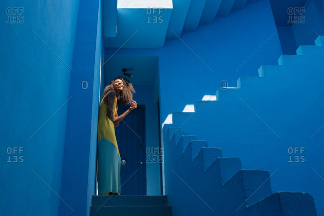 Black woman in a blue building stairs