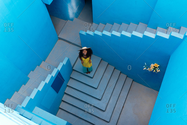 Black woman in a blue building stairs with a straw hat