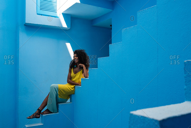 Black woman sitting in a blue building stairs.