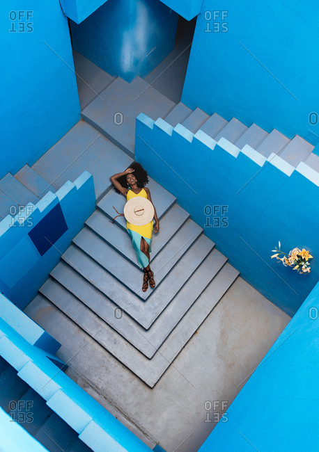 Black woman lying down in a blue building stairs