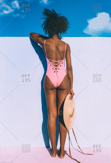 Black woman leaning in blue wall in a swimsuit