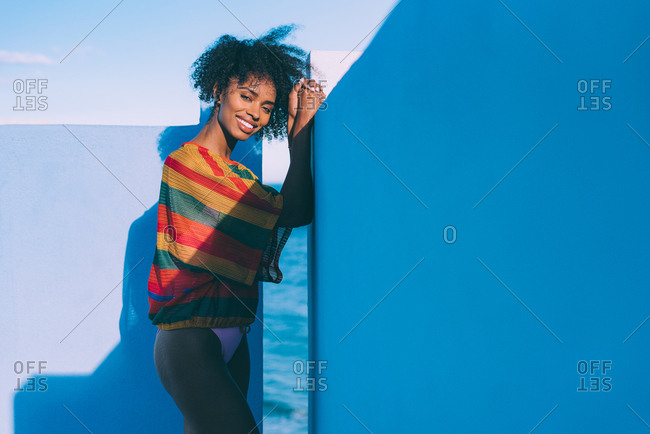 Black woman leaning in blue wall dressed in summer clothes