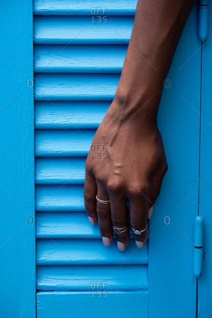 Crop woman hands with rings on a blue background windows