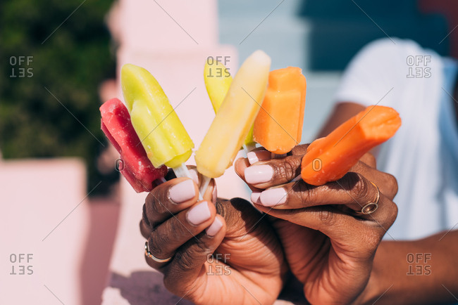 Black woman hands full of colorful popsicles