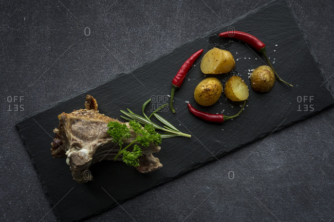 From Above a roast lamb on rectangular black plate
