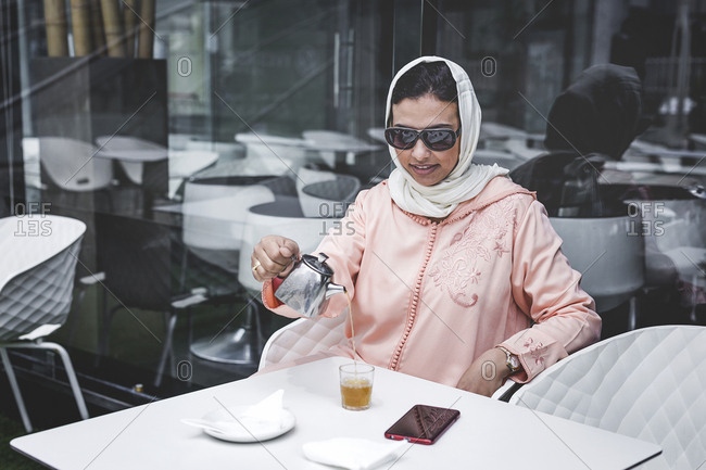Nice Moroccan woman with hijab and typical Arabic dress, drinking tea