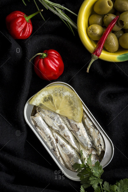 Close-up shot of yummy canned fish lying near hot peeper and bowl with olives on black cloth background.