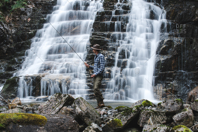 Fisherman dressed in fishing hat with blue shirt and gray marching trousers holding a spinning rod standing on rocks behind the slope of a waterfall