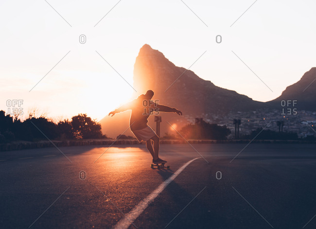 Back view of man riding on skateboard on asphalt road down the hill in backlit.