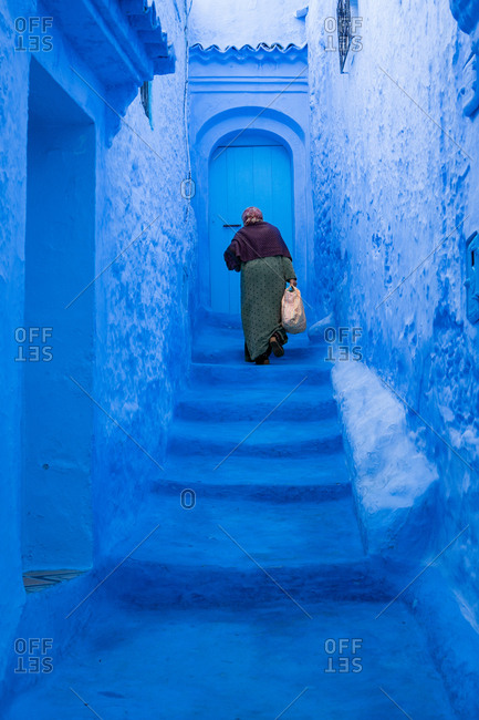 Old woman climbing the blue stairs