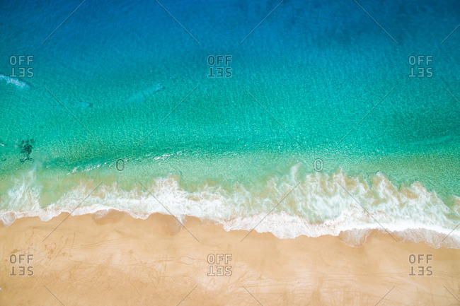 Aerial view of beautiful bright turquoise sea wave with clean white foam rolling up on light sandy beach on sunny summer day in La Graciosa, Canary Islands