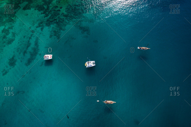 Aerial view of small colorful boats and rafts sailing in dark deep sea water on sunny summer day in La Graciosa, Canary Islands