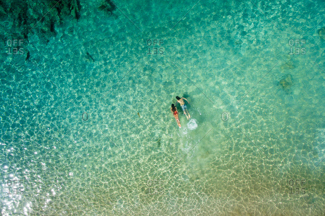 Aerial back view of relaxed man and woman swimming together underwater in beautiful clear turquoise sea water on sunny summer day in La Graciosa, Canary Islands