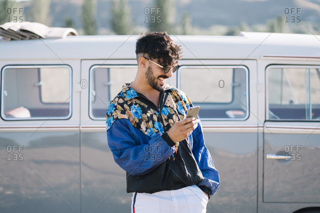 Attractive young guy in stylish outfit laughing and browsing smartphone while standing near vintage van in nature