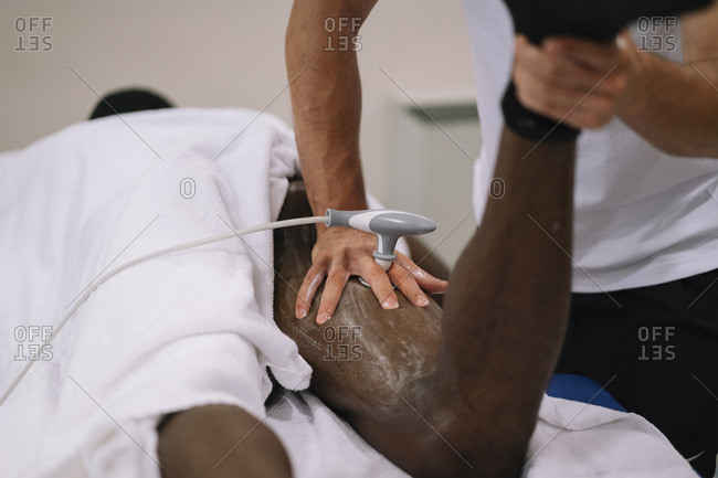 The physiotherapist treating a man using equipment for radio therapy