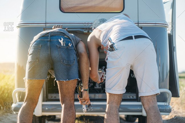 Back view of two guys fixing motor of retro van while traveling in nature together